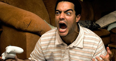 foto di un giovane che gioca alla play e si arrabbia