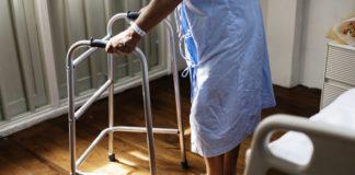 anziano che cammina appogiandosi ad un girello (sostegno fisico)