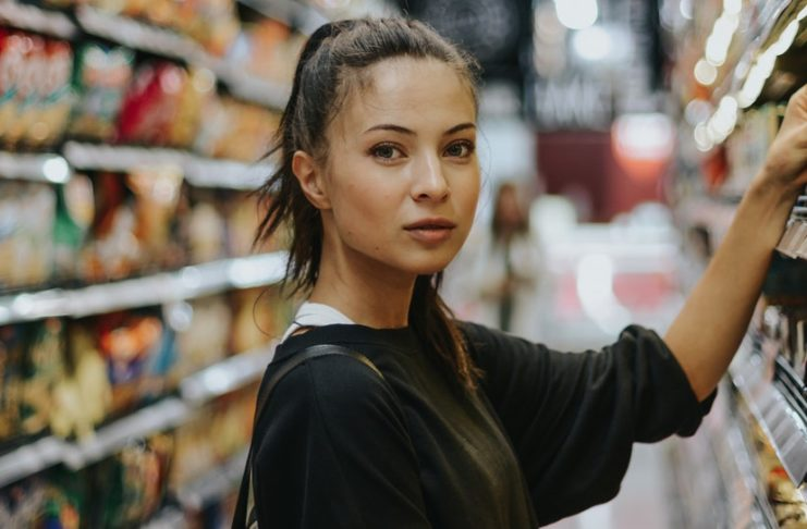 girl posing in front of a supermarket shelf