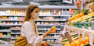 Comporta0mento dei consumatori al tempo del coronavirus: ragazza con mascherina in un supermercato