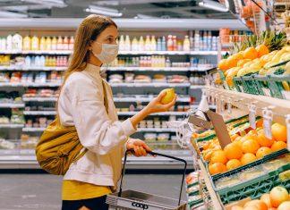 Comportamento dei consumatori al tempo del coronavirus: ragazza con mascherina in un supermercato
