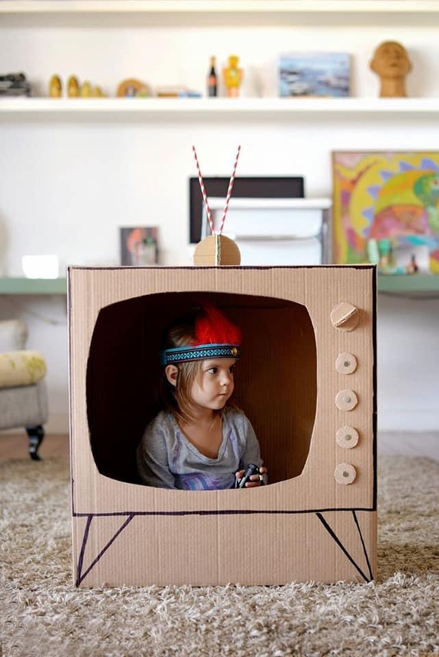 Una bambina che gioca dentro una televisione di cartone vestita da indiana d'america.