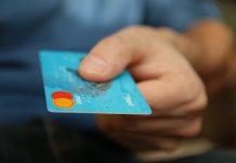 Digital Payments Contactless Una carta di debito tenuta in mano nel gesto di porgerla a qualcuno