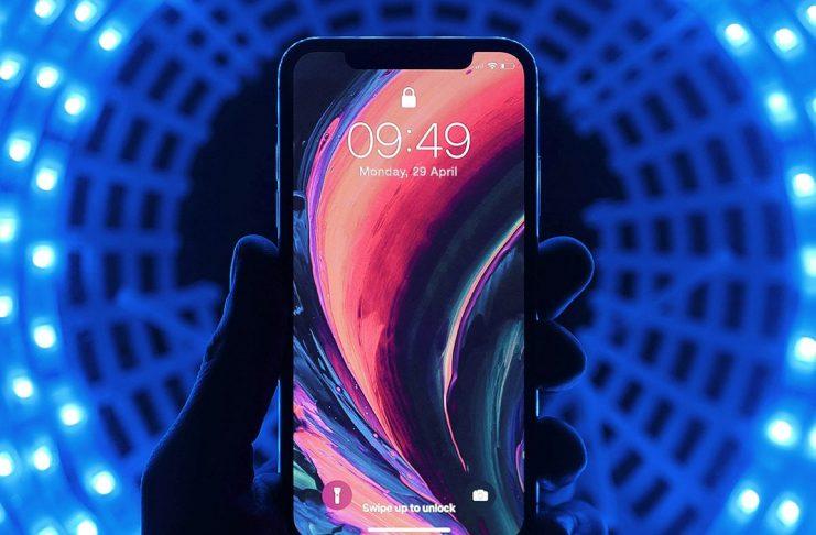 Il ruolo del mobile nella pandemia da Coronavirus, mano che tiene uno smartphone con schermo acceso e colorato. Sfondo blu con luci