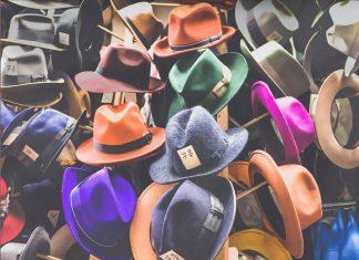 Insieme di cappelli colorati appesi in un mercatino vintage